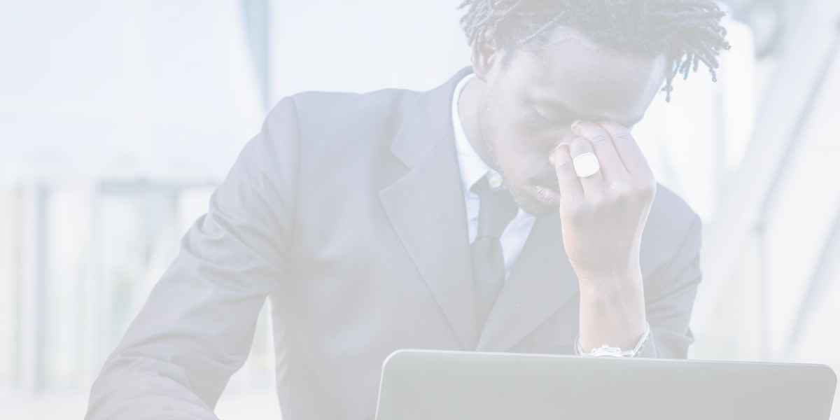 A black businessman using his computer outdoor. He is covering his face in a stress moment.